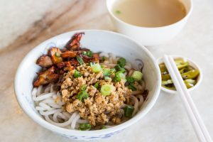 Delicious Chinese udon noodle with minced, BBQ pork and black source