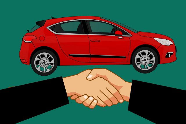 Image of handshake with car in background